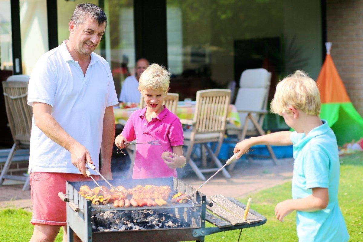 A father with sons, two twin teenage boys cooking meat on barbecue for summer family dinner at the backyard of the house