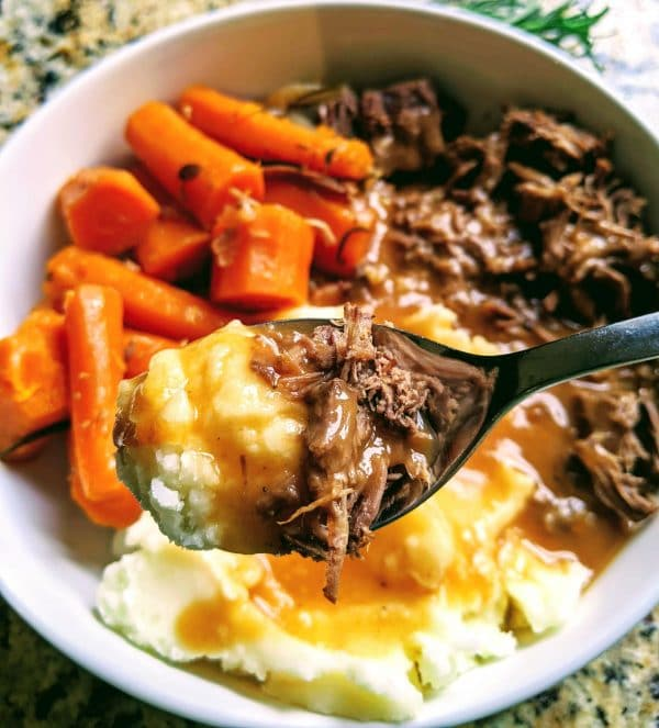 spoonful of pot roast and mashed potatoes over a bowl of the full meal