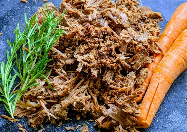 shredded roast beef by carrots and sprigs of rosmeary.